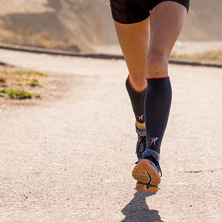 Close-up of runner's legs wearing compression calf sleeves in solid slate with Lily Trotters' bird logo at ankle
