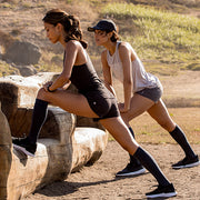 Two runners stretching & wearing solid slate compression socks