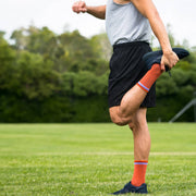 Male athlete in field wearing orange herringbone compression crew socks