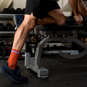 Male legs in weight room wearing orange herringbone compression crew socks