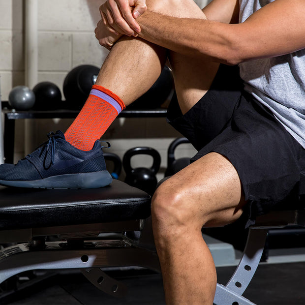Male feet in weight room wearing orange herringbone compression crew socks