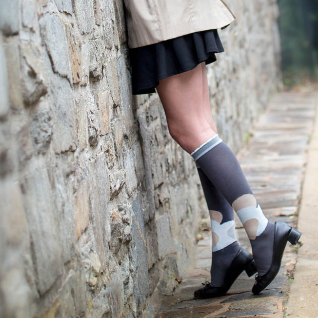 Woman in skirt and heels leaning against stone wall wearing grey compression socks with neutrals heart pattern