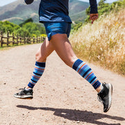 Runner in blue rocking Lily Trotters compression calf sleeves in blue stripes
