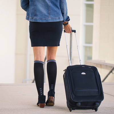 Traveler with suitcase wearing black compression socks with grey stripe at top and vertical grey XXXX on ankles