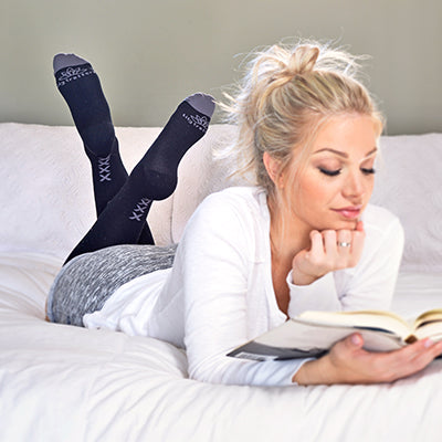 Woman reading on bed with legs crossed, wearing black compression socks with vertical grey XXXX on ankles