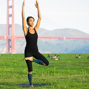 Woman doing outdoor yoga wearing slate polka-dotted compression calf sleeves