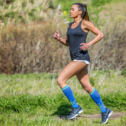 Female runner wearing blue compression socks with lotus flowers on front