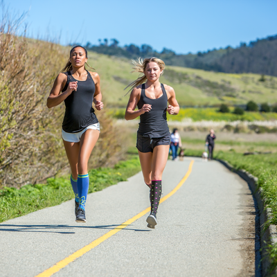 Woman running with friend & wearing black compression socks with pink and light blue dots