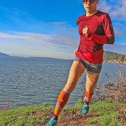 Designer performance compression socks with mountains on a moonlit sky in orange on trail runner sprinting a turn!