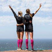 Two athletes looking into the distance with arms around each other, hands extended into air with peace signs, wearing hot pink polka dotted compression sleeves and socks