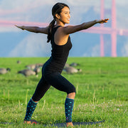 Woman doing yoga outdoors wearing slate polka-dotted compression calf sleeves