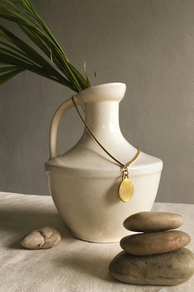 Contemporary brass jewelry with a long pendant charm. A modern necklace and modern jewelry