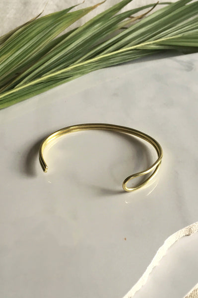 Adjustable modern brass bangle with in a contemporary jewelry style. Contemporary brass jewelry