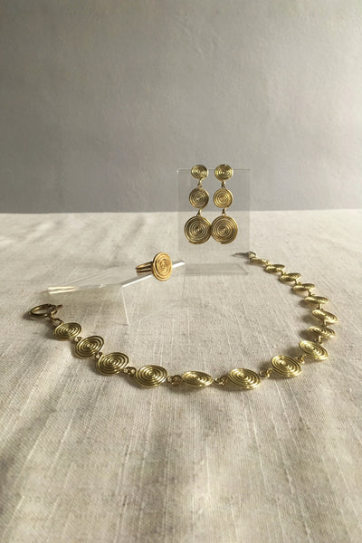 Modern jewelry with spiral charms. Contemporary necklace with an ancient, old-world jewelry style. Contemporary brass necklace