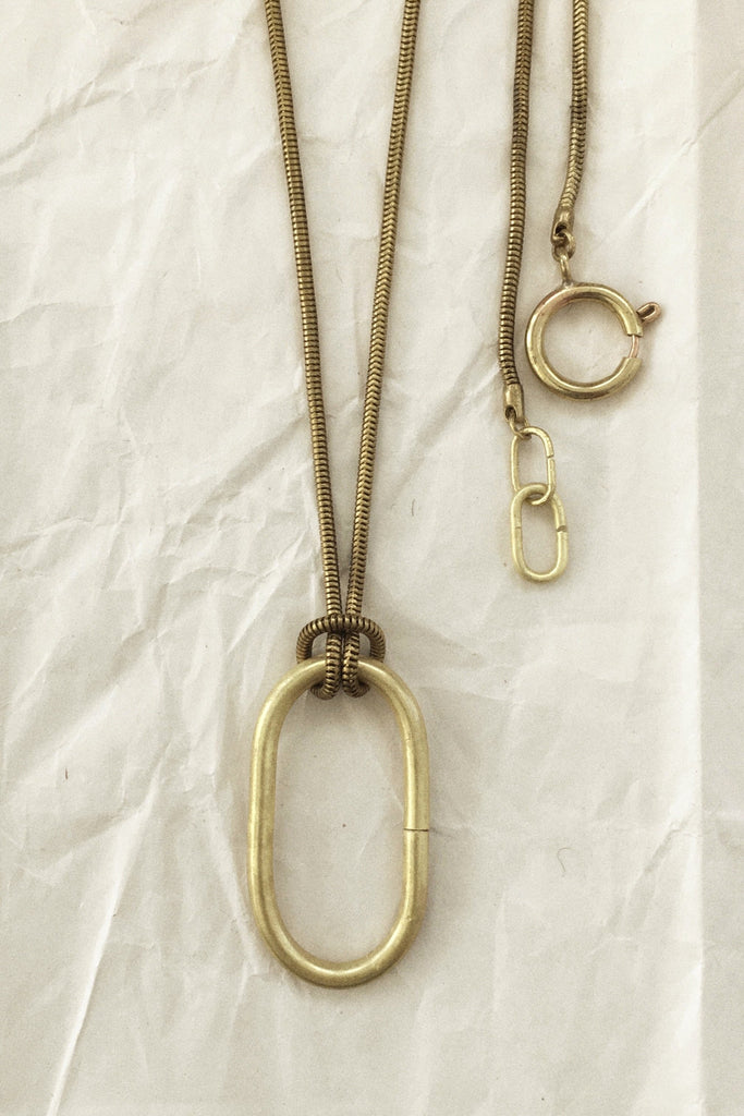 Handcrafted modern jewelry with an sleek pendant on a long chain. Contemporary necklace or contemporary brass jewelry.