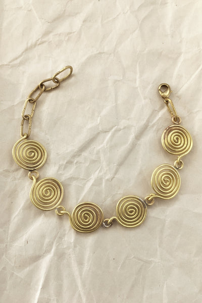 Modern jewelry with spiral charms. Contemporary bracelet with an ancient, old-world jewelry style. Contemporary brass bracelet