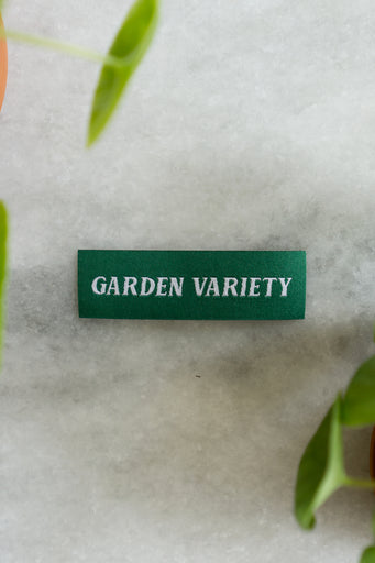 "Small woven rectangular patch in kelly green with white text reading ""garden variety"""