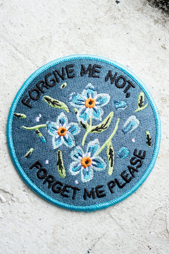 "Round embroidered patch in blue with central floral design encircled by the words ""forgive me not, forget me please"""