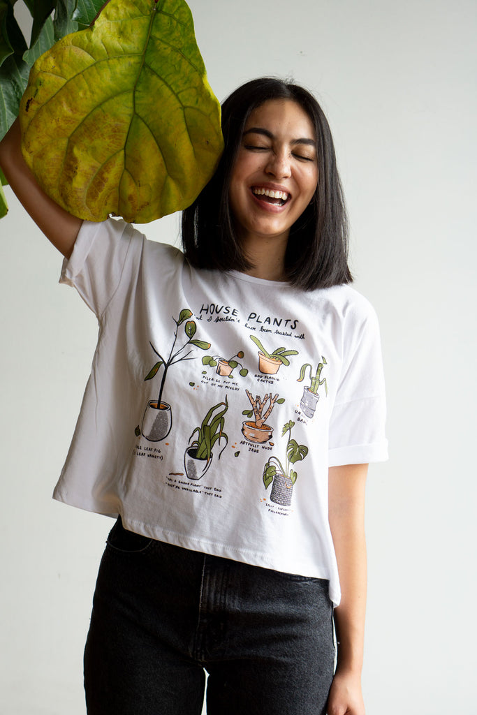 Model wearing white crop top with illustrations of dying plants and funny captions