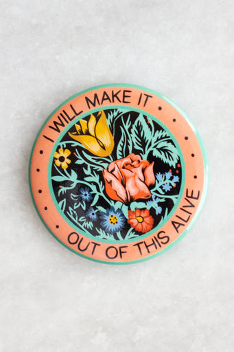 "Round magnet with central floral design encircled by the words ""I will make it out of this alive"""