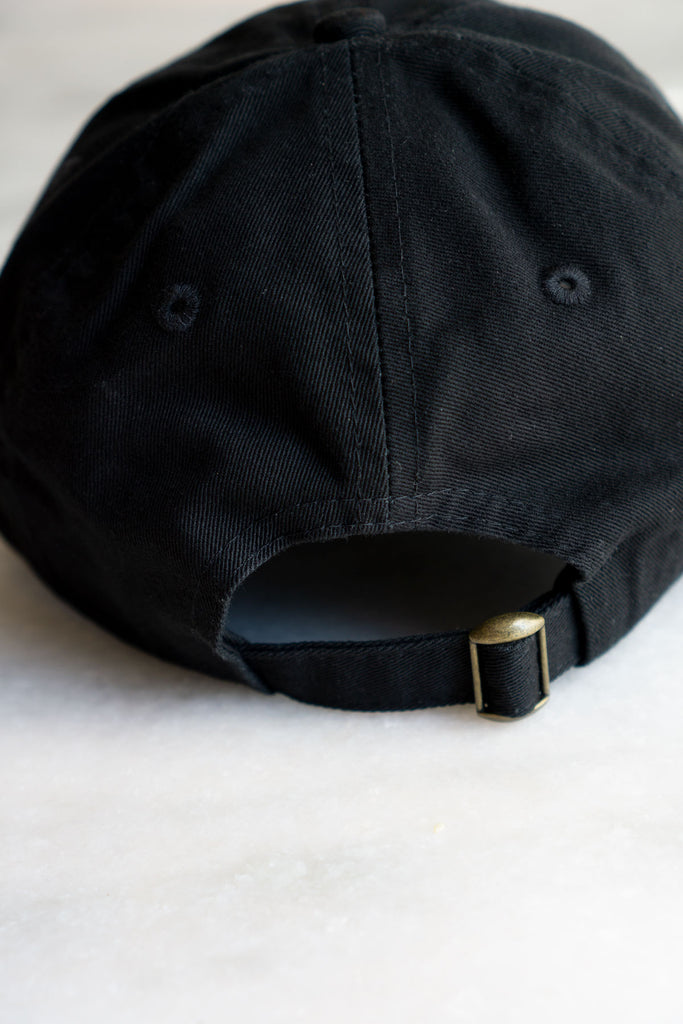back of black baseball hat with brass sliding clasp