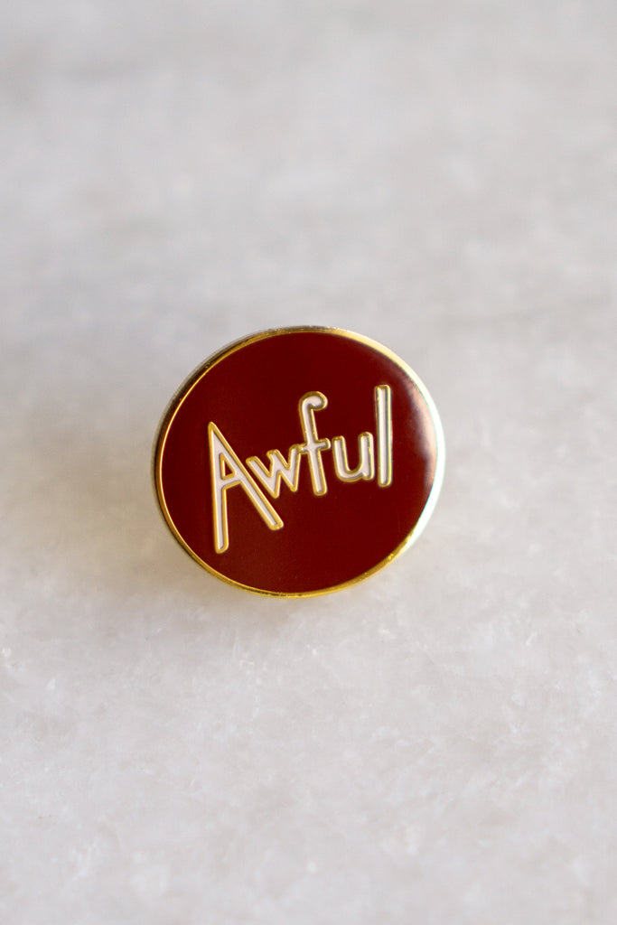 "circle enamel pin of white text reading ""Awful"" on dark red background"