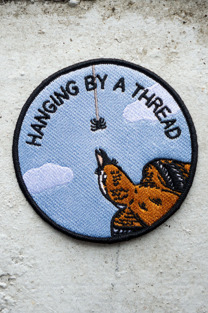 "Round embroidered patch featuring imagery of a bird about to eat a spider that's hanging from a single thread of webbing. The text reads ""hanging by a thread"""