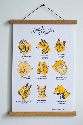 print hung with wooden hanger white background with nine yellow dogs with dark blue outlines and text that reads dogs feeling things title and names like disappointed bloodhound and bemused samoyed etc