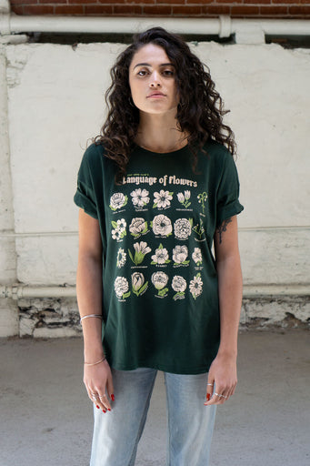 Model wearing loose fitting dark green t-shirt with pink print of flowers and funny sarcastic captions