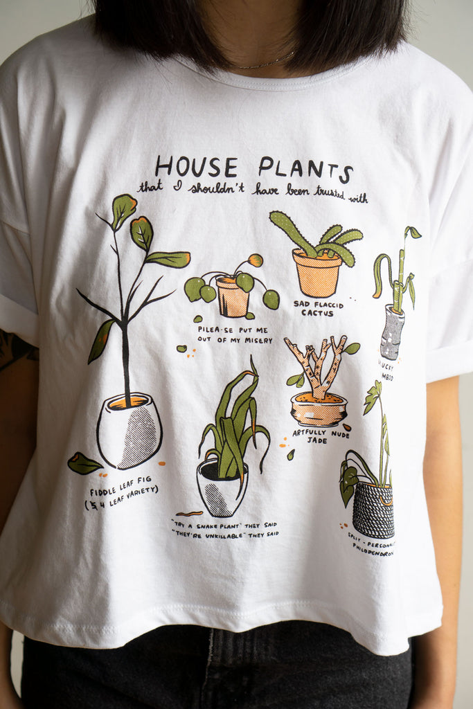 Close up on white crop top with illustrations of dying plants and funny captions