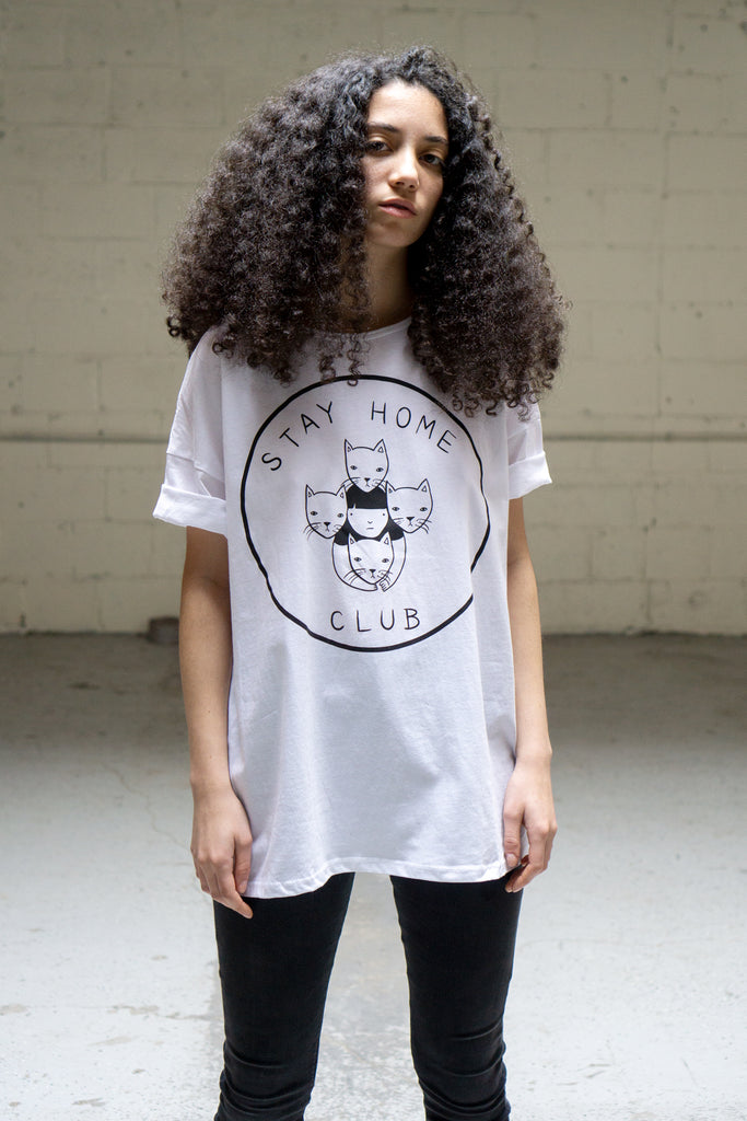 "Model wearing white loose fitting shirt printed with a logo of a girl surrounded by 4 cats and the words ""Stay Home Club"""