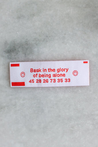 "Small rectangular woven patch in the style of a fortune cookie insert, with red text reading ""bask in the glory of being alone"""
