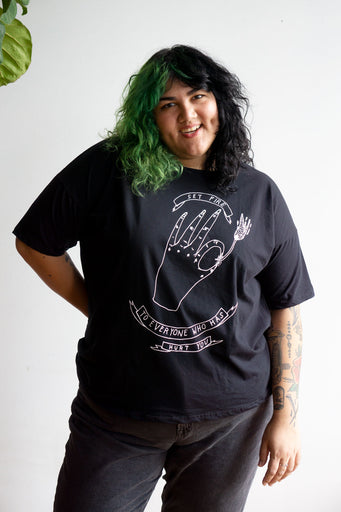 "Model wearing loose fitting black t-shirt with illustrated print of a hand lighting a match and readin ""set fire to everyone who has hurt you"""