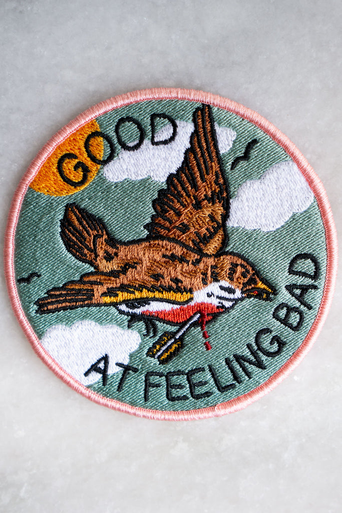 "Round embroidered patch with imagery of a robin flying in the sky with an arrow piercing its chest encircled by the words ""good at feeling bad"""