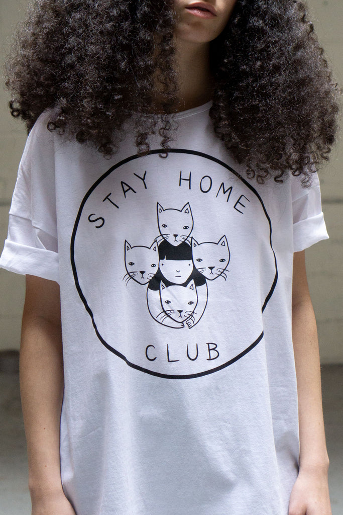 "Close up shot of loose fitting shirt printed with a logo of a girl surrounded by 4 cats and the words ""Stay Home Club"""