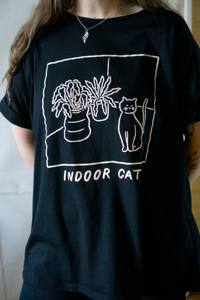"Close up on black loose fitting t-shirt with printed illustration of a cat and potted plants and slogan ""indoor cat"""