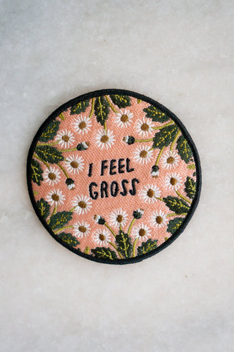 "Round embroidered patch in pink with daisy flower motif around the edge, and text in the centre reading ""I feel gross"""