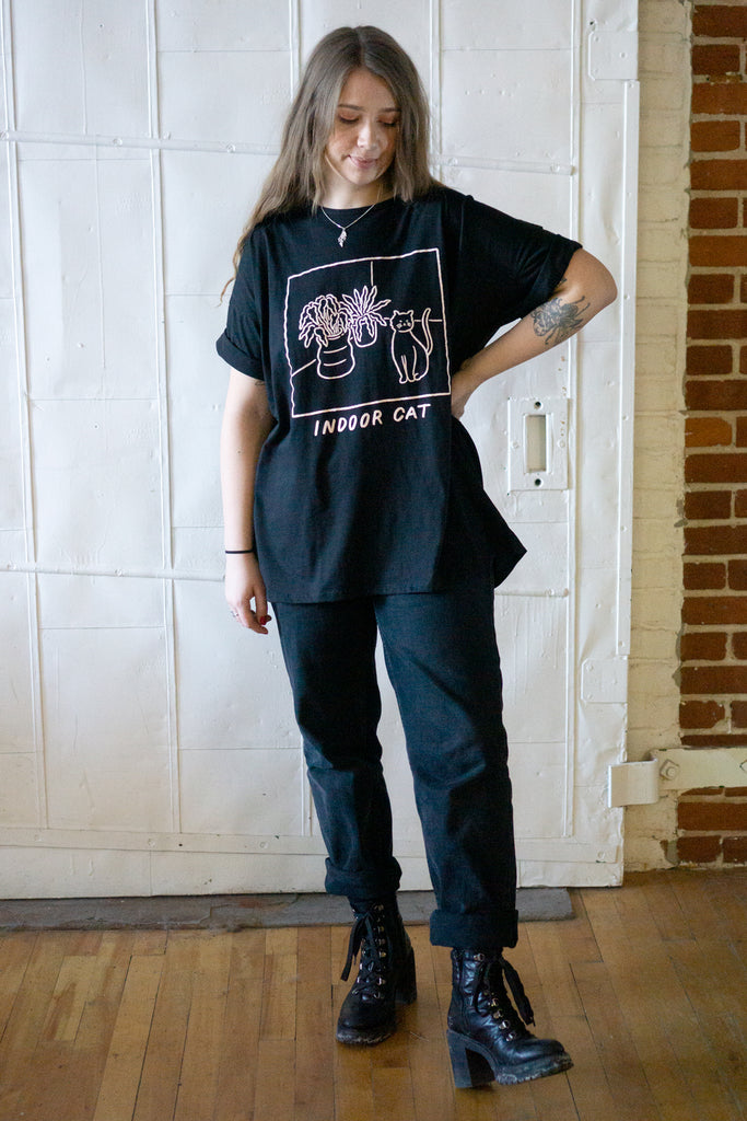 "Model wearing black loose fitting t-shirt with printed illustration of a cat and potted plants and slogan ""indoor cat"""