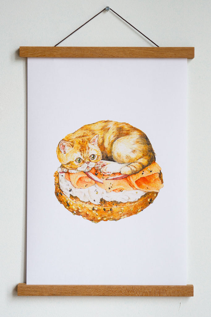 art print with orange cat sitting on bagel with cream cheese smoked salmon and onions