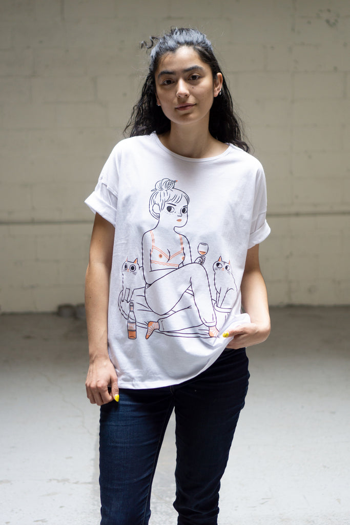 Model wearing white loose fit t-shirt with print of naked woman drinking wine with her cats
