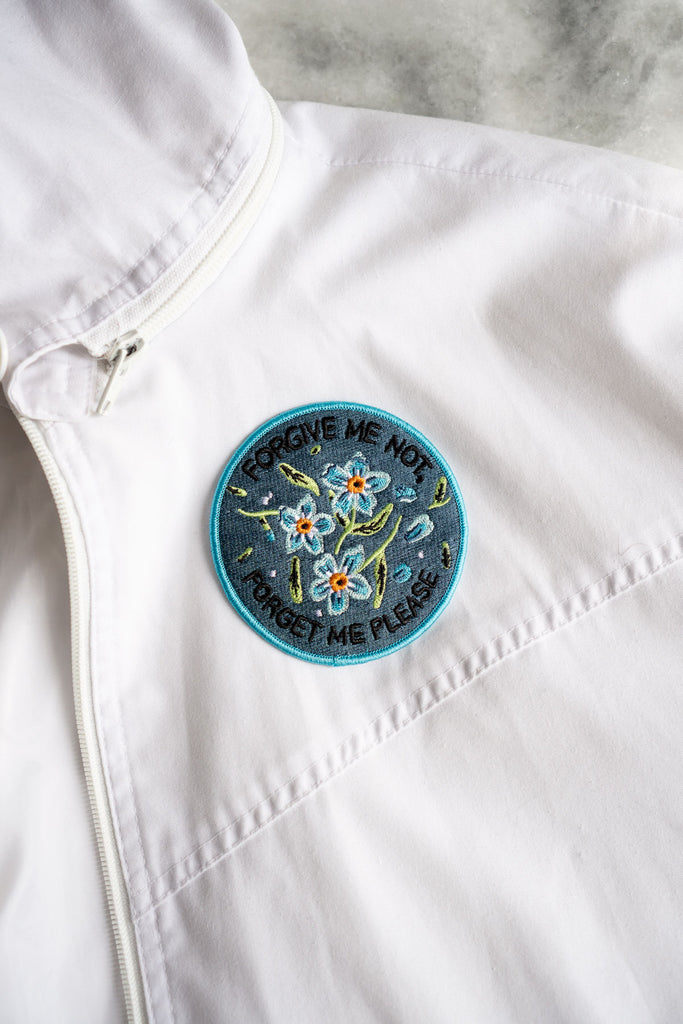 White jacket with blue floral patch on the chest