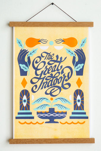 wooden hanger holding yellow paper with dark blue light blue and orange hands and flowers and leaves with text reading the great indoors in calligraphy in the middle
