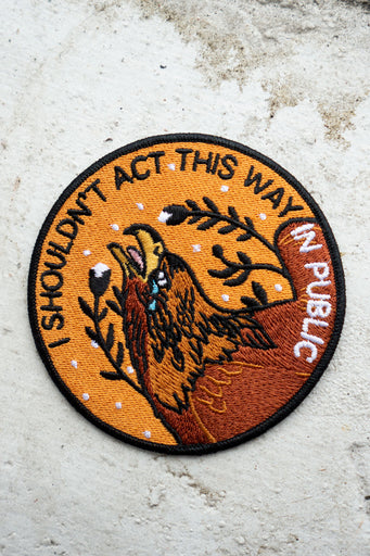 "Round embroidered patch in tones of yellow and brown with imagery of a crying eagle and the words ""I Shouldn't Act This Way in Public"""