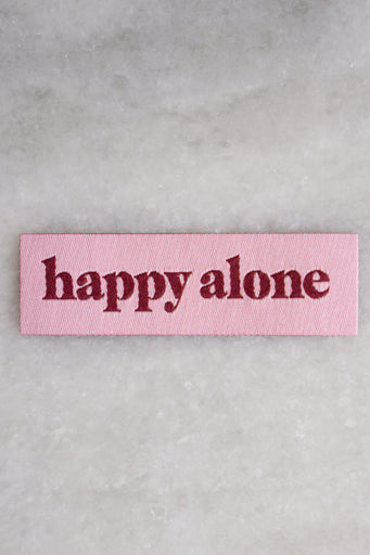 "Small rectangular woven patch in pink with maroon text that reads ""happy alone"""