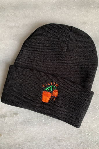 black beanie winter hat with dying orange flower in flowepot and killin it text