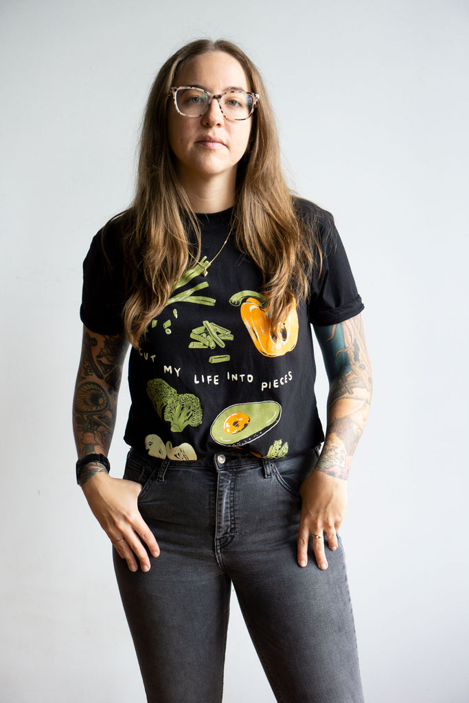 "model wearing funny black t-shirt with sliced vegetables print and the Papa Roach lyrics ""cut my life into pieces"""