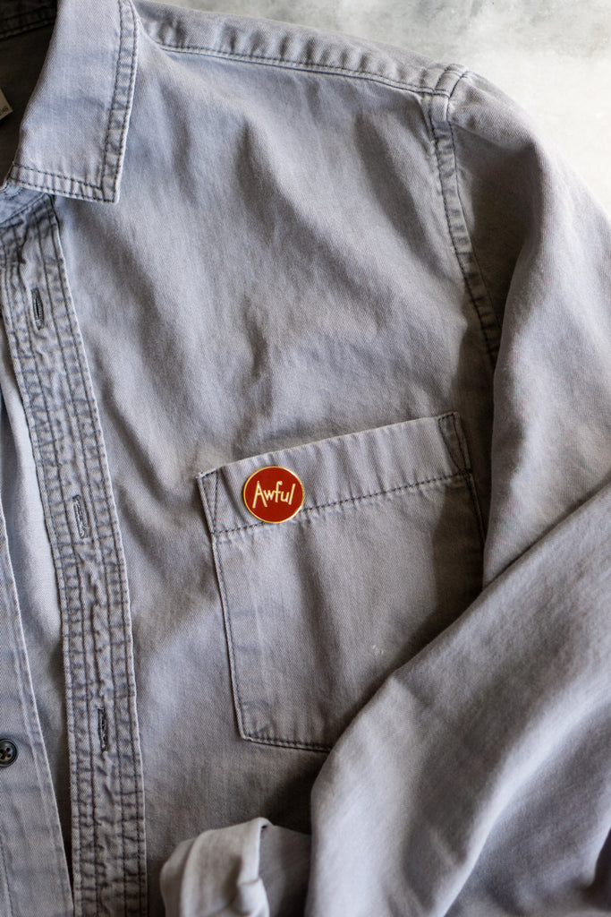 "circle enamel pin of white text reading ""Awful"" on dark red background pinned on pocket on grey denim button up shirt"