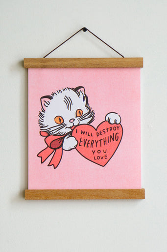 white cat with orange eyes and red bow on pink background holding red heart with black text inside that reads i will destroy everything you love