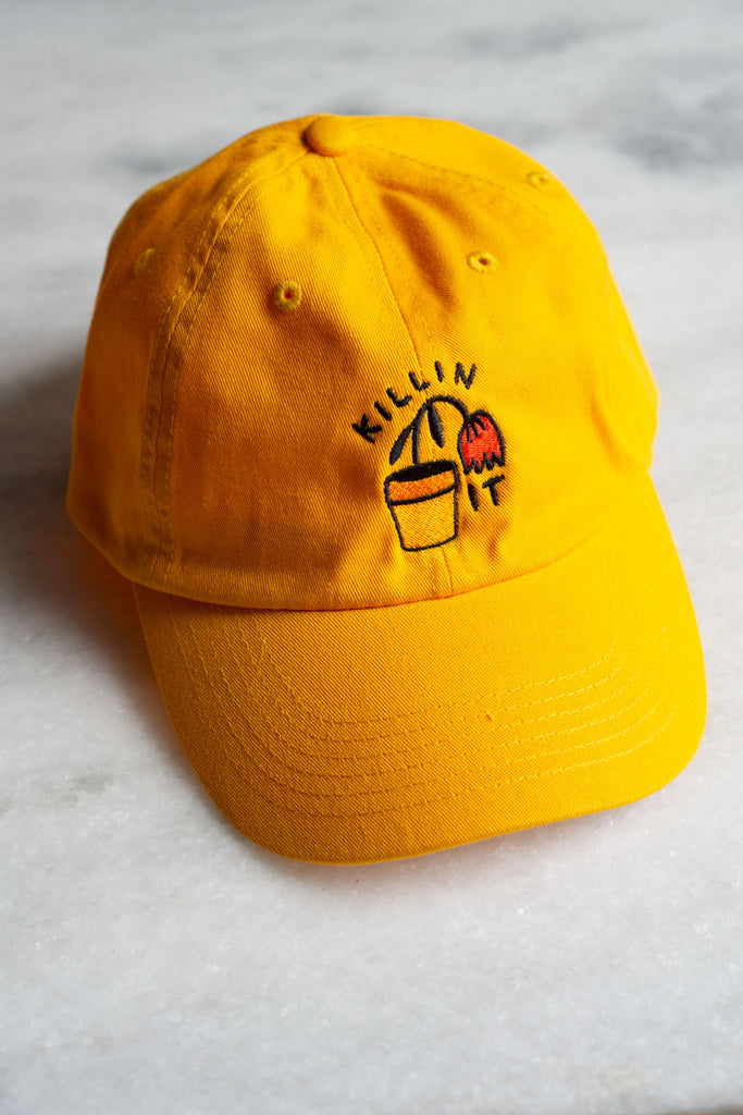 yellow baseball hat with black embroidered text reading killin it with red flower drooping out of yellow flower pot