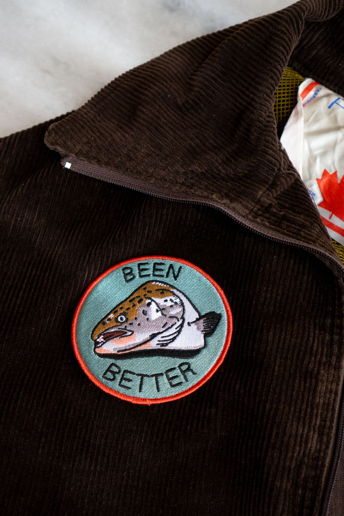 "Round embroidered patch with a fish head design and the words ""Been Better"" on the chest of a brown corduroy jacket"